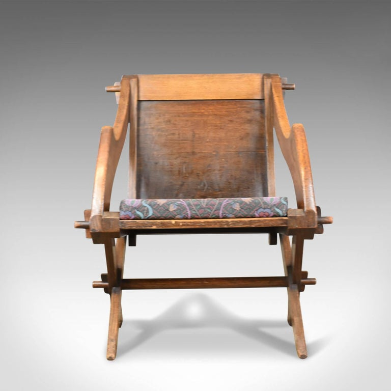 This is an antique Glastonbury chair, English Tudor Revival hall seat dating to the early 20th century, circa 1900.  A fine Glastonbury chair faithful to its origins Exhibiting ecclesiastical and gothic overtones Classic tusked joints, the