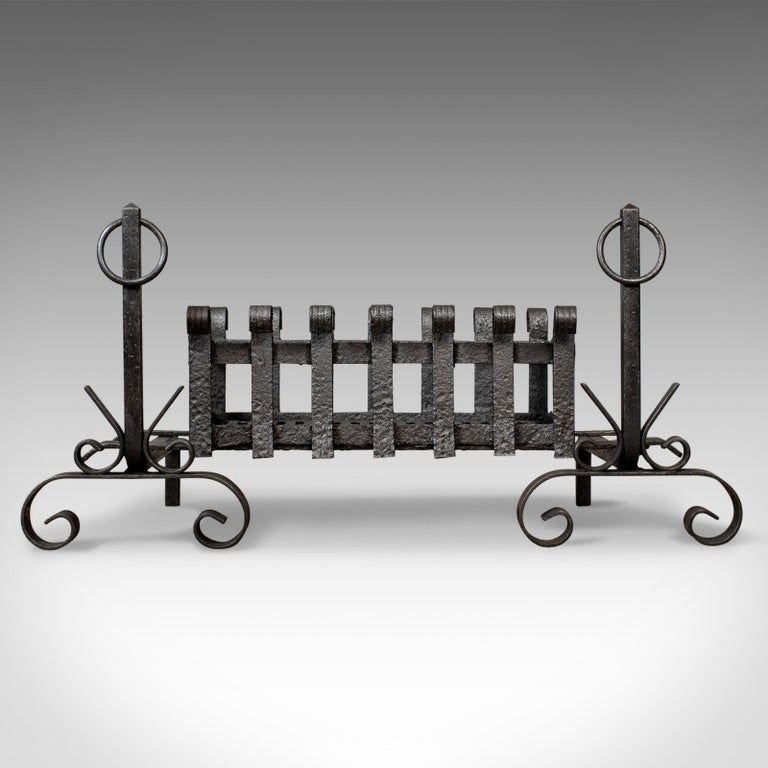 This is an antique fire basket and andirons, or fire dogs, an English, Victorian fireplace accessory with a removable iron grate dating to the early 20th century, circa 1900.  A fire basket raised on andirons presented in very good condition A