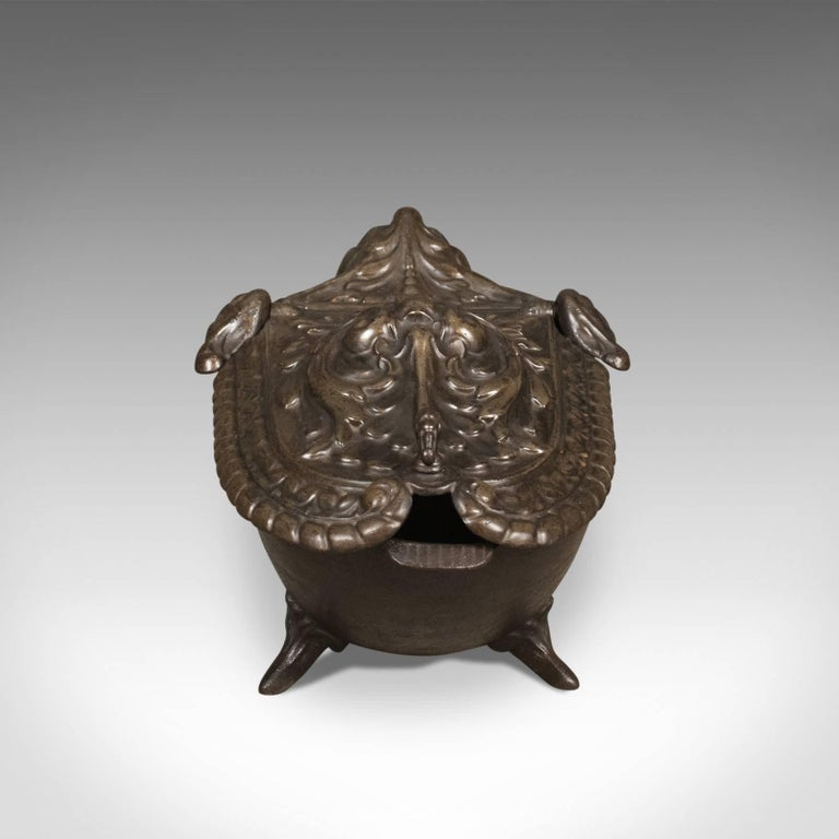 This is a period Art Nouveau coal scuttle, an antique Victorian fireside bin in iron dating to circa 1900.  Bronzed finish over iron bowl Impressive high relief pressed lid over voluminous storage Featuring free-form garlands and sprays framed