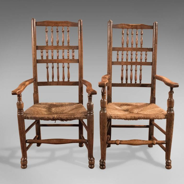 A harlequin set of Georgian, spindle back, rush seated, dining chairs comprising five singles (three and two) and two carvers dating to circa 1800.  Crafted in traditional oak, ash and elm Wonderfully rich patinated original wax finish and
