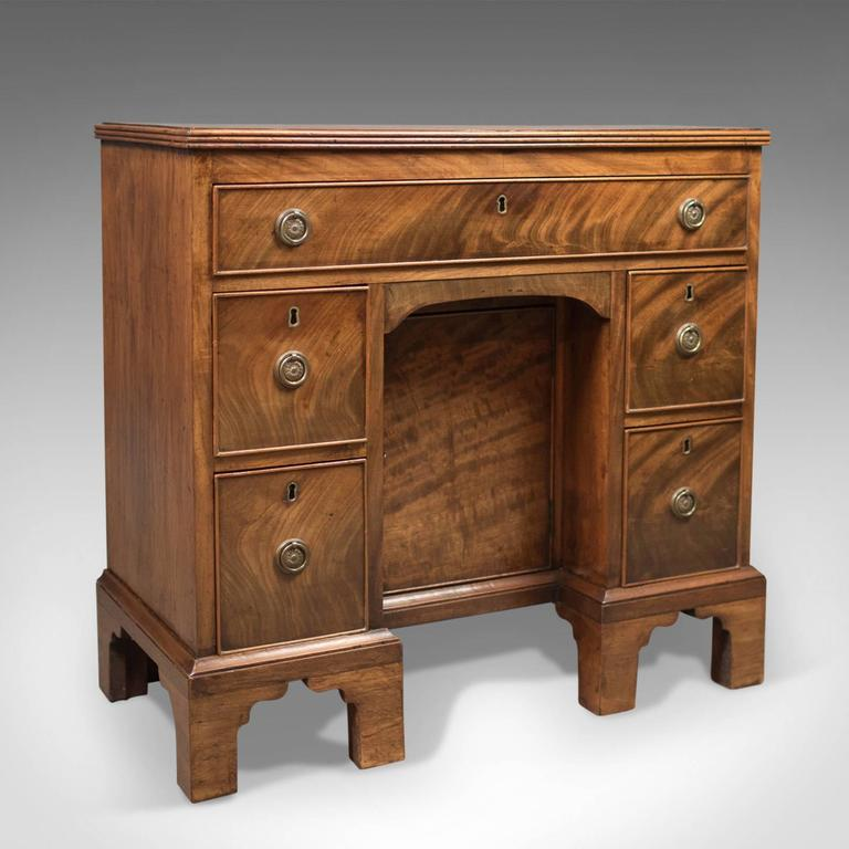 This is an antique kneehole desk, late 19th century, Victorian in the Georgian taste, circa 1870.