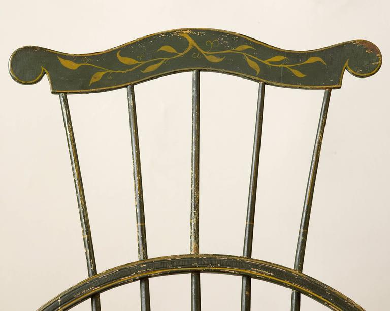 A New England comb-back Windsor side chair featuring an original green-painted finish accented with yellow striping and foliate decoration on the crest. Likely produced in Rhode Island or Massachusetts, this Windsor side chair is further enhanced by