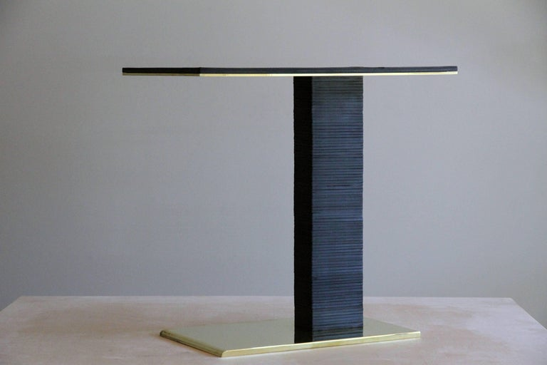 The cantilever infinity side table was inspired by Paul Dupré-Lafon's use of stacked leather in his designs for Hermès. The base is solid brass, bevelled at the front, and mirror polished on all sides. Over eighty pieces of leather are stacked to