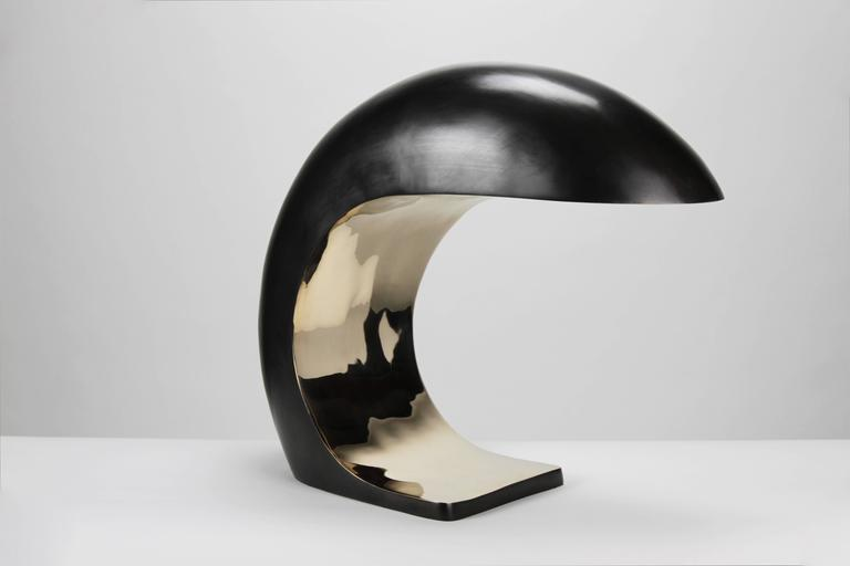 The Nautilus Study table lamp is inspired by Mid-Century Italian design.  It is cast bronze and weighs up to 28 pounds. The outer shell has a blackened patina and the face is high polished to a mirrored finish.   The Nautilus illuminates by a
