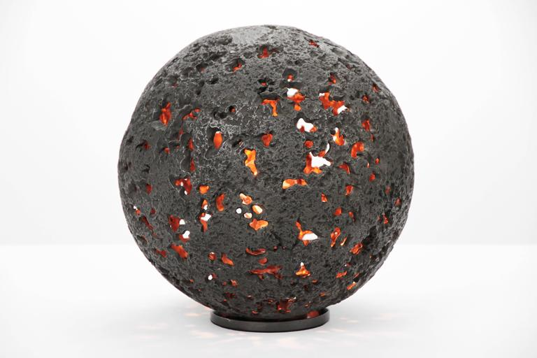 The Hot Planet Table Lamp is a sphere full of craters with a light source at the center symbolizing the core of energy within a planet.  The body is cast in bronze with a blackened patina. The patina brings out the texture in the sculpture.  The raw