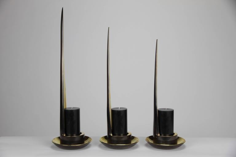 "The Stiletto candle holders in brass are a collection of three.  The severe yet soulful shape is inspired by women's beauty rituals.   The light from the 6""H x 2.5"" diameter black pillar candles brightens as the candle fades away and the"