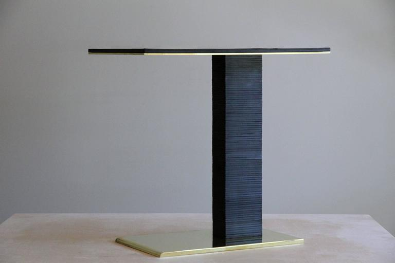 The Cantilever Infinity side table was inspired by Paul Dupré-Lafon's use of stacked leather in his designs for Hermès. The base is solid brass, beveled at the front, and mirror polished on all sides. Over eighty pieces of leather are stacked to