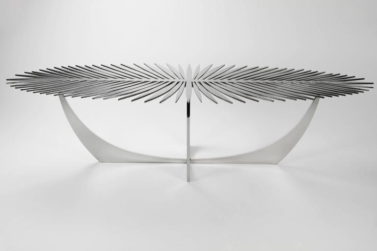 The double frond coffee table is made of high polished solid stainless steel. When lit from above, the table top creates beautiful shadows on the floor while also reflecting its surroundings. The Double Frond Table works well sculpturally without
