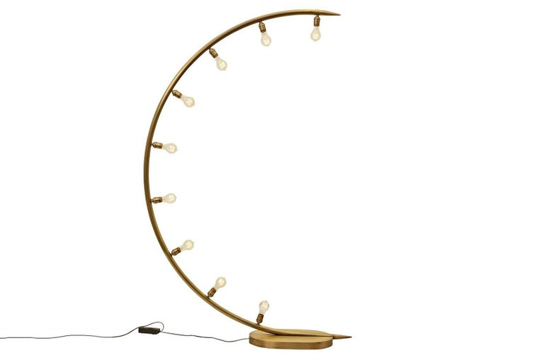 The crescent moon floor lamp is made of hand forged brass with a oiled bronze finish and has nine medium bulb sockets. The bulb choice dramatically changes the look and vibe of the lamp as well as its effect on the room. Nine Edison style bulbs are