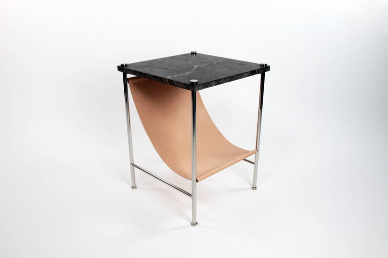 The leather sling side table is the perfect solution for keeping magazines and books tidy while having useful table space.  The body is made of stainless steel and the top is black marble with seashell fossils.   Made in Los Angeles.