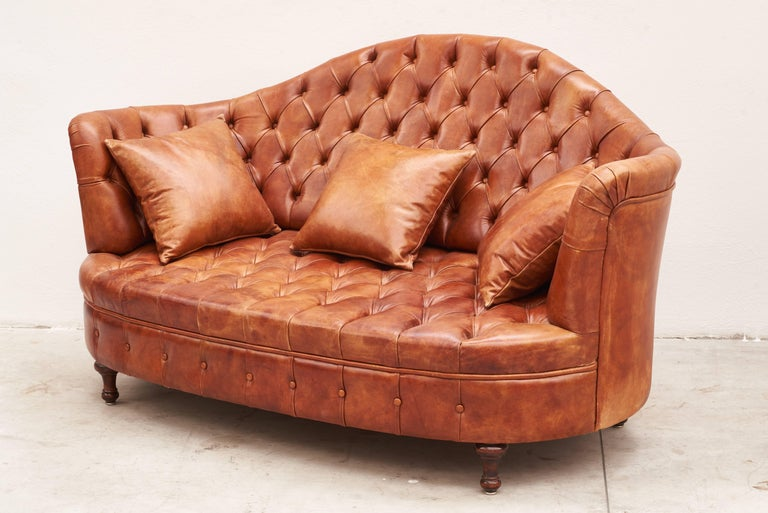 Leather Italian Chesterfield sofa with three leather pillows.