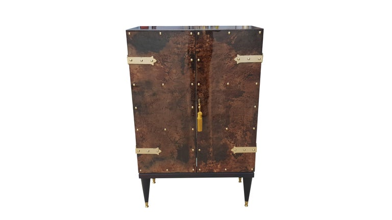 This two door dry-bar cabinet make for an ease of accessibility to the interior which is fitted with glass shelves.  The middle shelf is horse-shoe shaped for taller bottles.  Mahogany and brass legs, lacquered goatskin.  This is definitely the
