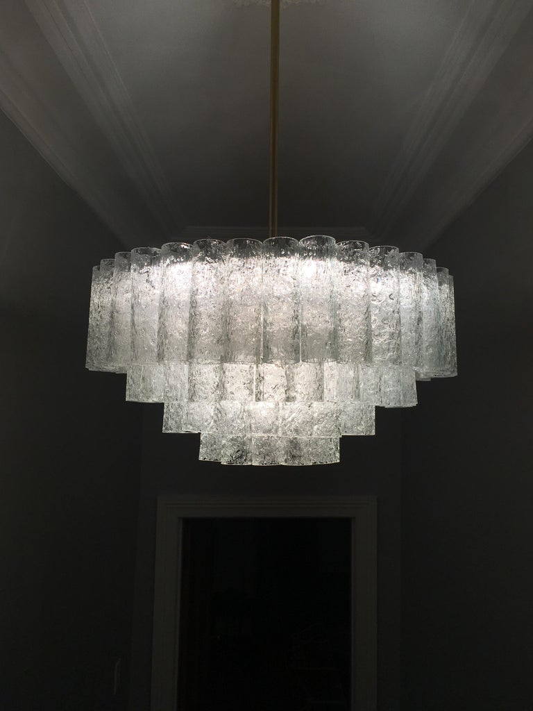 This elegant chandelier by Doria of Germany was made in the 1960s. It's a Classic piece of modernist design. The chandelier consists of a brass ceiling cap and rod, a painted aluminium alloy frame and four rings of textured glass tubes. The tubes