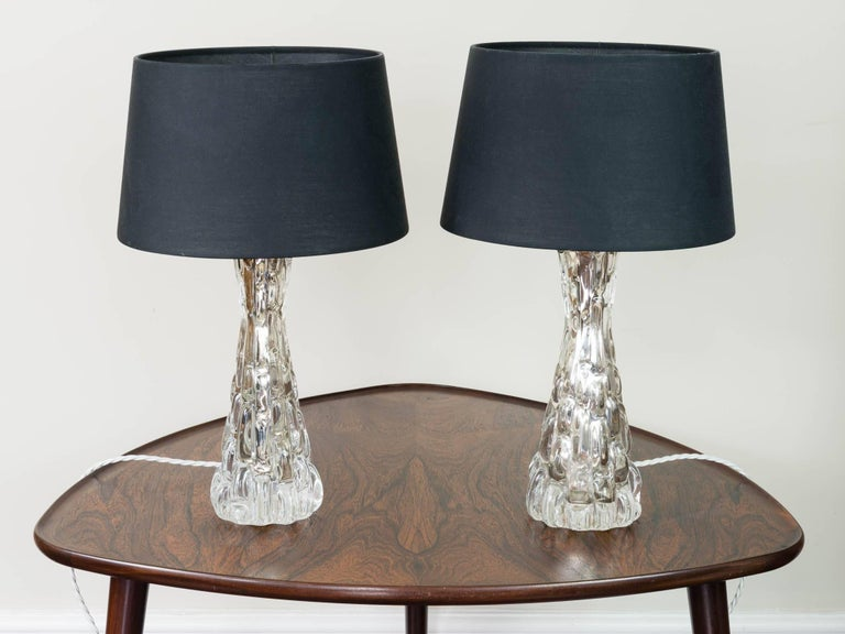 Pair of 1950s beautiful small relief glass table lamps by Orrefors Designed by Carl Fagerlund, Sweden and created from molded glass with chrome rods which run through the centre of each light to conceal the flex. The internal rod is designed to