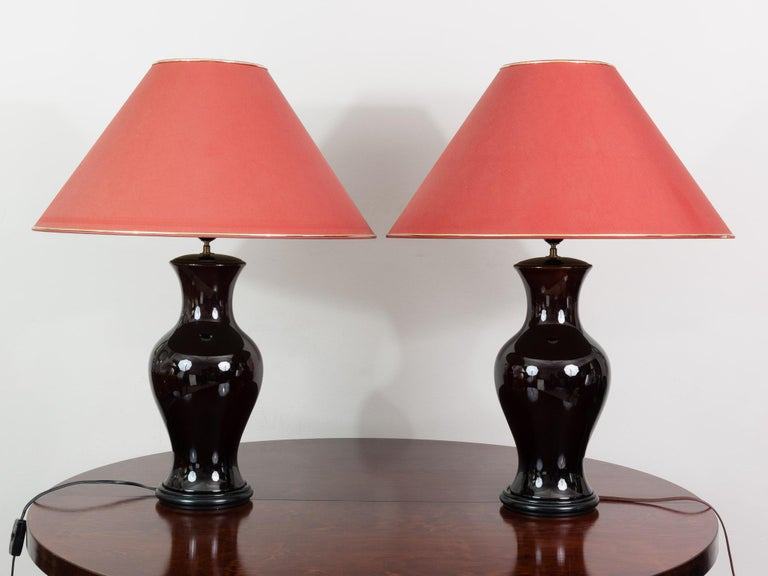 Pair of traditional Belgium dark brown glazed ceramic lamps with black wooden bases. The lamps still retain their original oversized original mauve shades with feature gold edging on the top and bottom. An on/off switch sits on the core of each