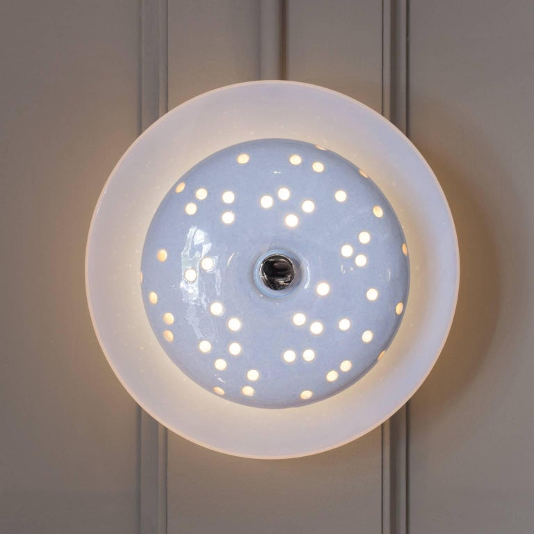 Inspired by the bioluminescent carapace of certain deep-sea creatures, our Perforata lighted sculptures are comprised of a hand-thrown, glazed, and perforated stoneware object floating atop a membranous cast glass lens and dimmable LED. From our