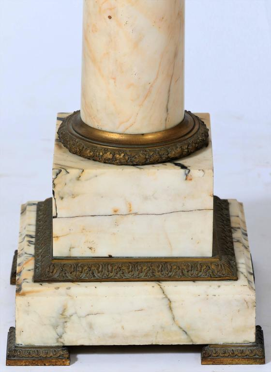 Large column or pedestal in Carrara marble with decorative elements and bronze feet, France, end of the 19th century.