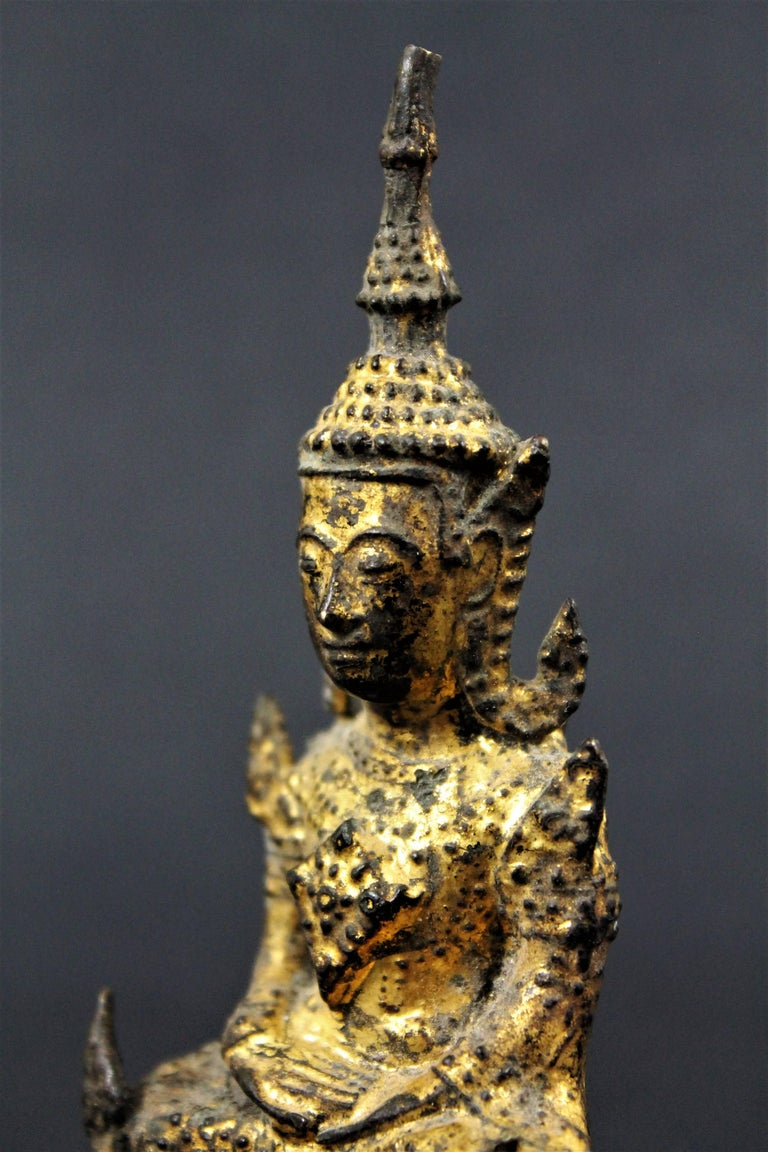 19th Century Thai Siam Rattanakosin Buddha Guilt-Lacquered Bronze Buddha seated in deep meditation (Virasana) on a stepped throne. The Unisa or flame above the head symbolizes attainment of Nirvana or is indicative of supreme knowledge.