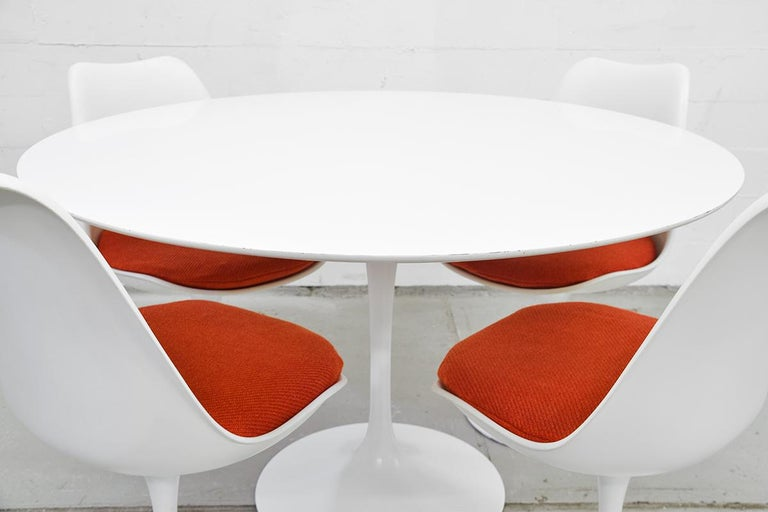 This midcentury Tulip dining set was designed by Eero Saarinen for Knoll International in the 1970s. The set is fully original and consists of four static Tulip chairs with the original Orange cushions and an original Tulip laminated table. The