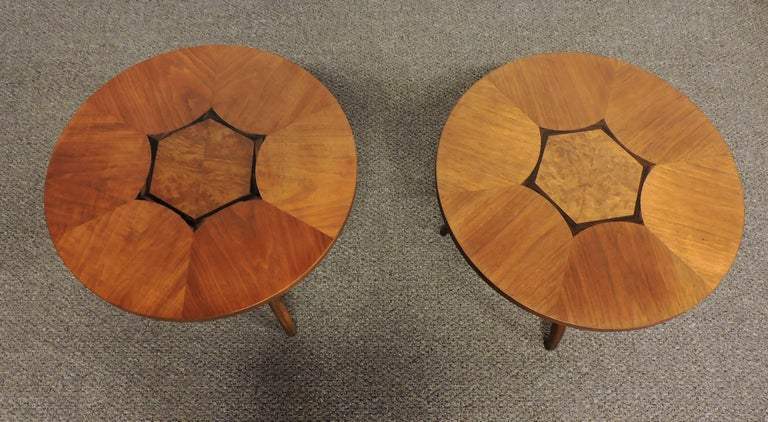 Beautiful pair of round walnut end tables made by high quality furniture manufacturer, Drexel. These tables have graceful curved tripod legs and a round inlaid wood top with a striking geometric design. Marked Composite by Drexel on bottom.