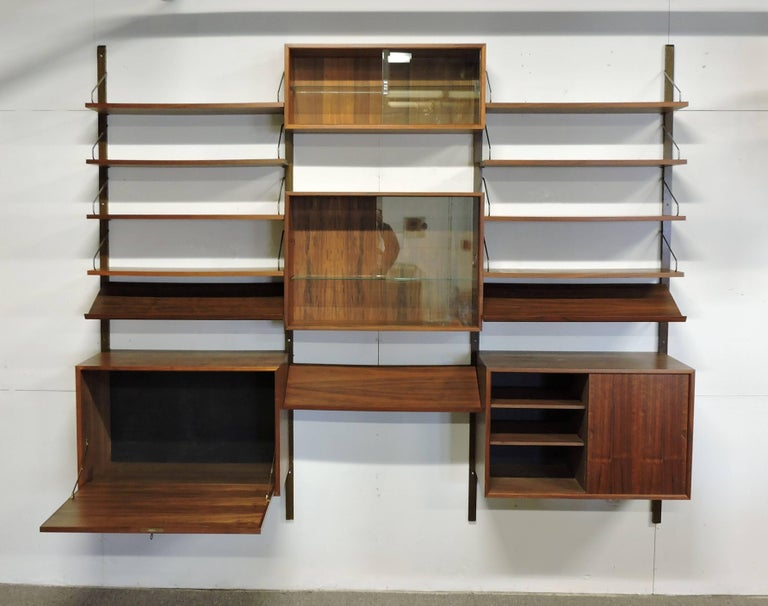 Large three bay Royal system wall unit designed by Poul Cadovius and made in Denmark. This unit includes four poles, four modules, eight shelves and three hard-to-find magazine shelves. Two of the cabinets have sliding glass doors, each with a