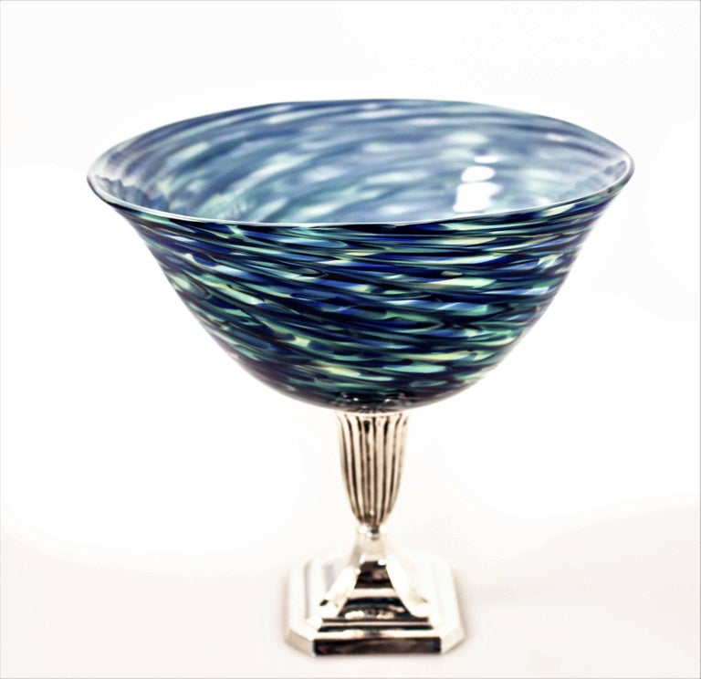 Different shades of blue, from light to dark with touches of pale yellow blend together in the glass like waves in an ocean. Sitting proudly on a sterling pedestal, this piece is great for practically anything you want to put inside. Or, leave it on