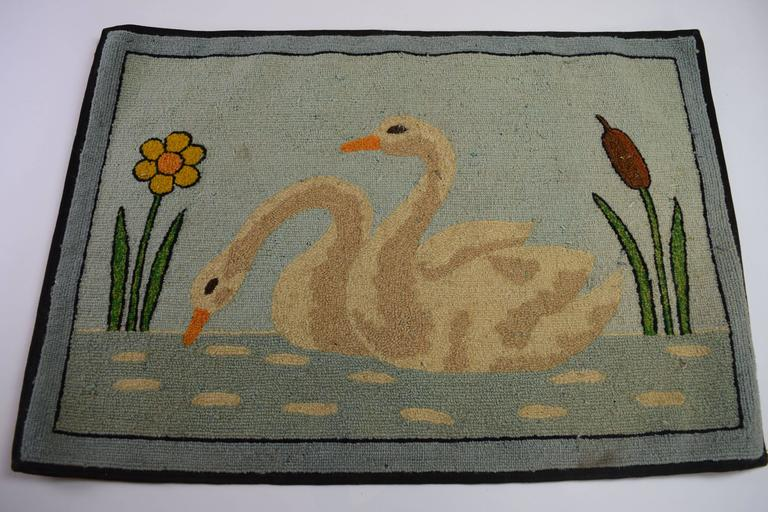 Folk Art hooked mat of a pair of swans on water flanked by a flower and reed.