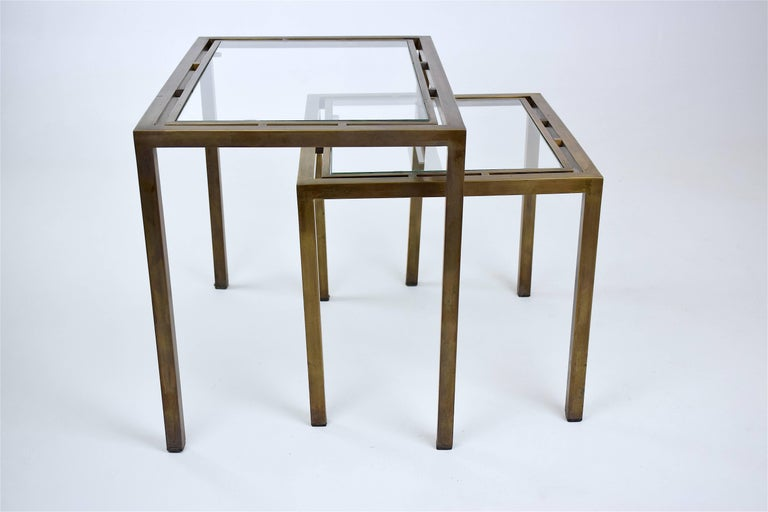 Graphic set of two 20th century vintage Mid-Century Modern nesting, side, end or coffee tables composed of solid aged brass and clear glass.  Designed in France, circa 1970s.  Measurements:  37 x 55 x 42.5 cm 37 x 43 x 34.5 cm