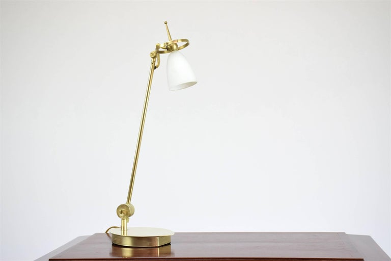Stunning 20th century desk office lamp in polished brass with beautiful geometrical design at the top, light switch on the leaf shaped base and milk glass shade. The lamp articulates at the shade and at the base. Perfect for desk and writing tables.