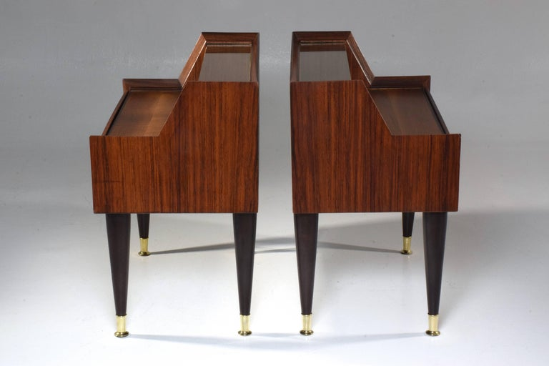 Pair of 20th century Italian vintage nightstands in fully restored condition designed in the style of a mini secretary composed of rosewood veneer, glass and polished brass endings.  These side tables are designed with a central drawer, a top glass