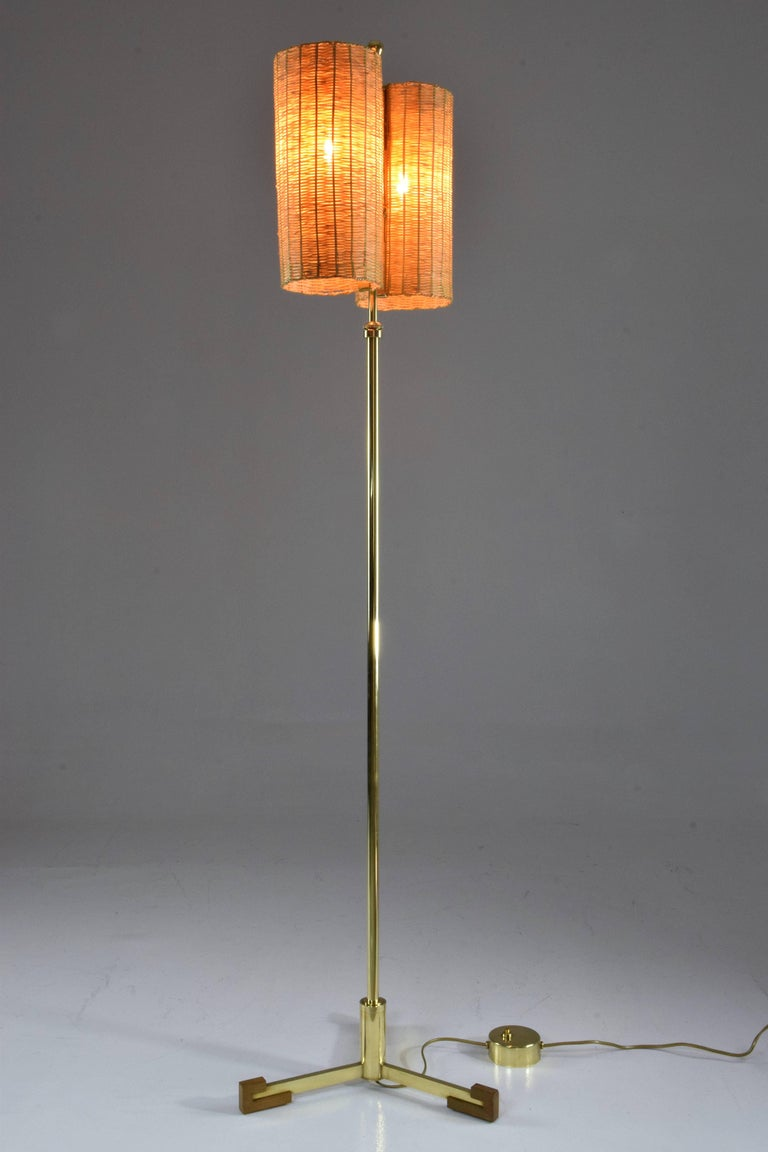 Equilibrium Definition: when opposite forces are in total harmony   Contemporary handcrafted floor lamp composed of a solid polished brass structure which adjusts in height, a brown hand pleated leather detail, a walnut tripod base and two