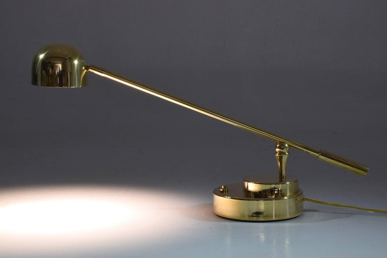 Contemporary handcrafted desk or accent lamp composed of a solid polish brass structure and designed with an adjustable stem and a rotatable shade. This piece rotates around two axis: the shade and the base. The Continuum-I Model III is part of the