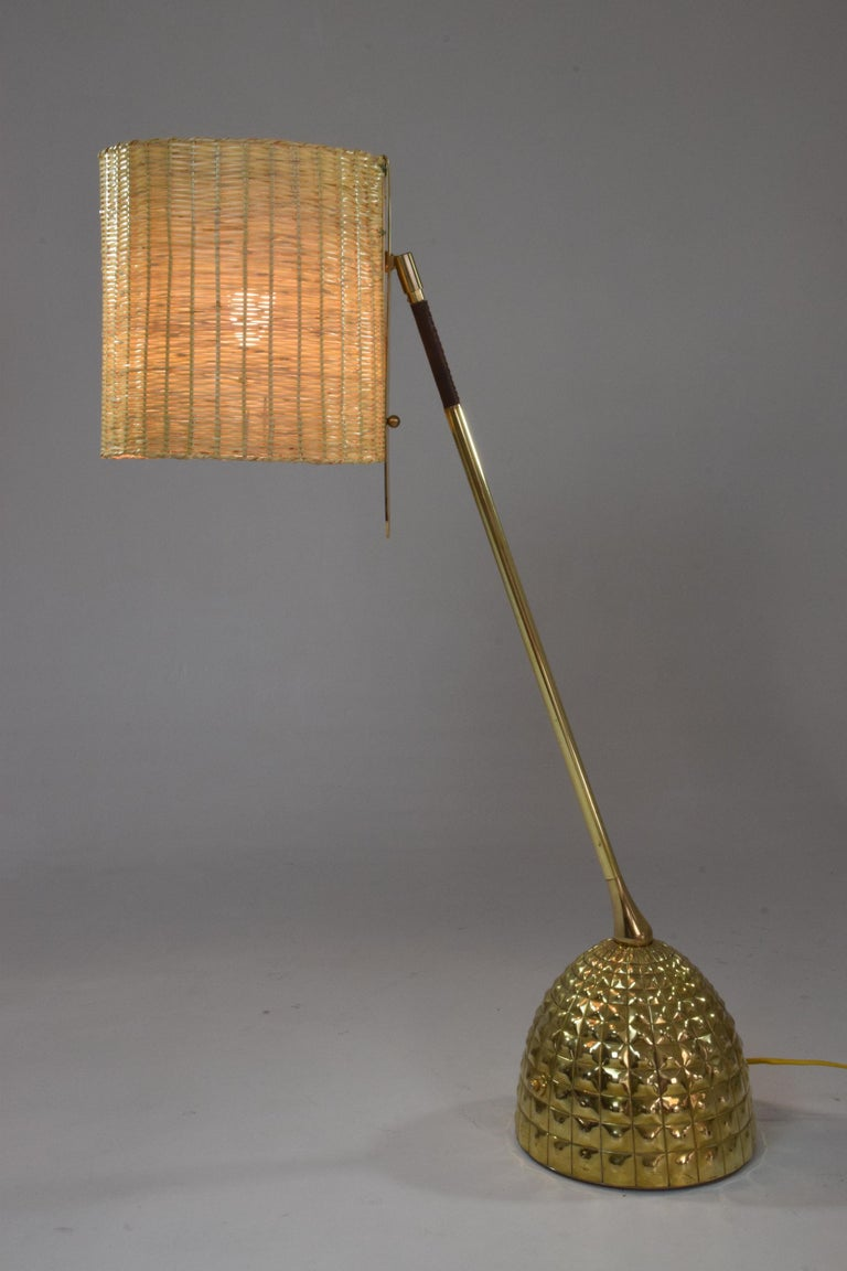 Contemporary handcrafted articulating table lamp of considerable size in polished brass and a hand-sewn sheathed leather detail, hand embellished base, built with our signature pear shaped joint and handwoven wicker shade. The shade is built with a