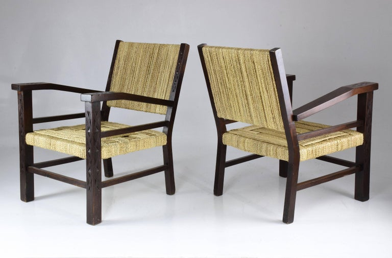 A 20th century vintage collectible pair of fully restored beechwood armchairs with a raked back and seat built of intertwined rope strings by Francis Jourdain, built in France, circa 1930s. This pair is adorned with beautifully carved details on the