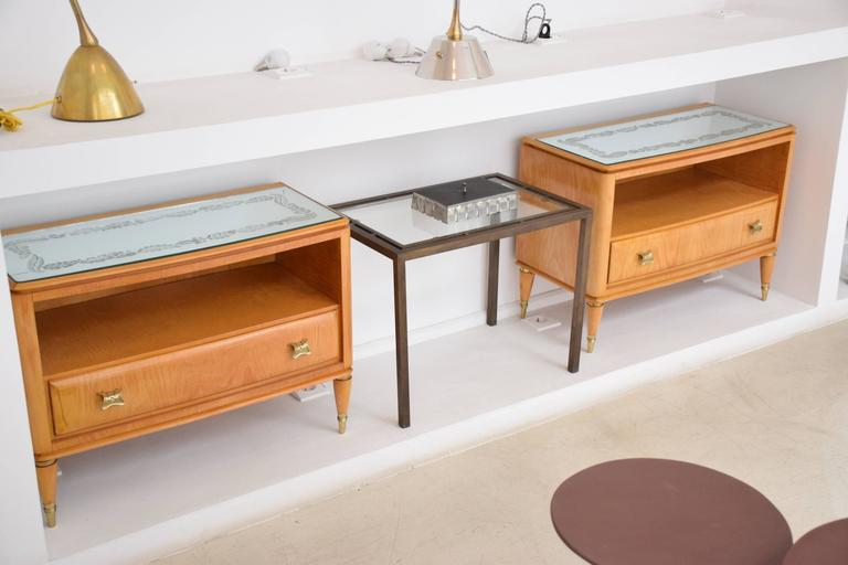 Beautiful pair of 20th century vintage Italian nightstands or bedside cabinets, circa 1950s composed of the original flower patterned engraved glass tabletop, a maple wood structure and cone shaped legs with brass details. It is composed of a drawer