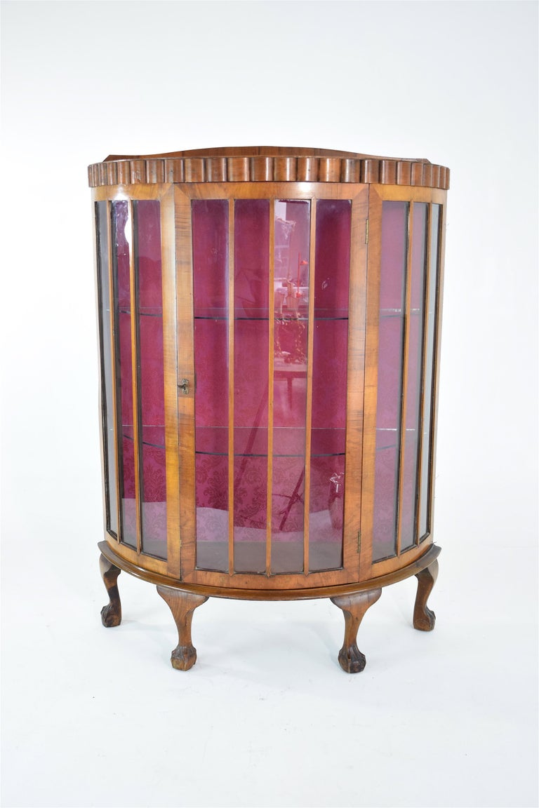 A french 20th century vintage demi-lune vitrine or display cabinet composed of oak and sitting on four cabriole legs. The interior is adorned with a vibrant pink flower motif upholstery. This beautiful storage piece opens with the center glass keyed