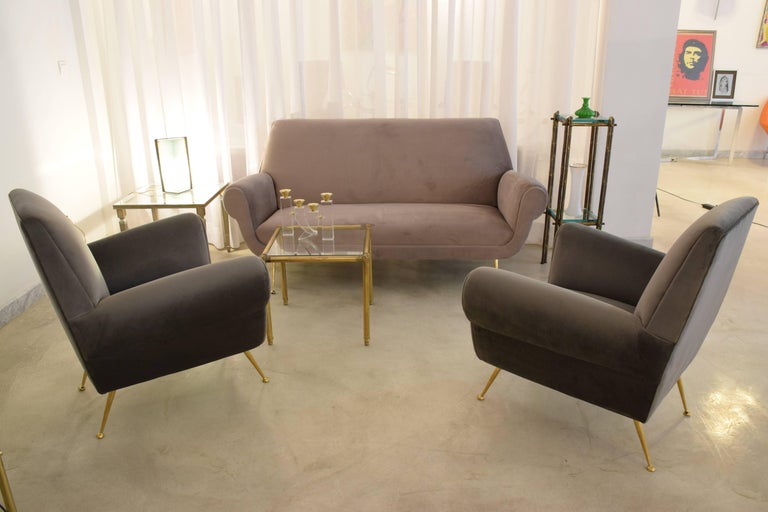 20th century vintage sofa attributed to Italian mid-century designer Gigi Radice reupholstered in a grey velvet sitting on splayed polished brass legs with an elevated effect.  Two armchairs in the style of a slightly darker shade are also