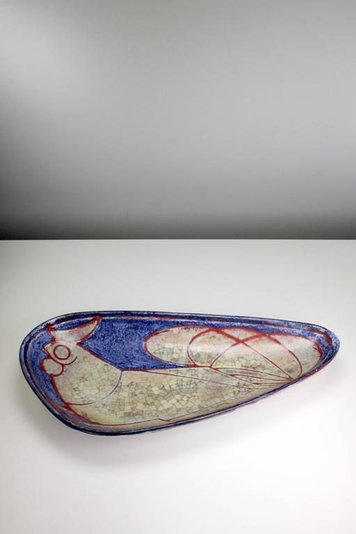 Handmade and hand decorated Danish modern plate / centerpiece by Marianne Starck for Michael Andersen & Son. Depicting a rooster in blue, red and warm beige colors. Smooth light glaze on the back. The Persia glaze was developed by Michael Andersen's