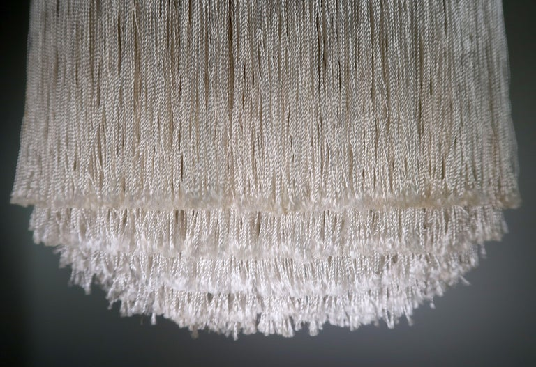 Swedish elegance! Scandinavian Mid-Century Modern extraordinary pendant by the great Swedish designer Hans Agne Jakobsson. Five separate layers of cream white colored silk fringes with brass frame and original brass stem. One E27 bulb hidden