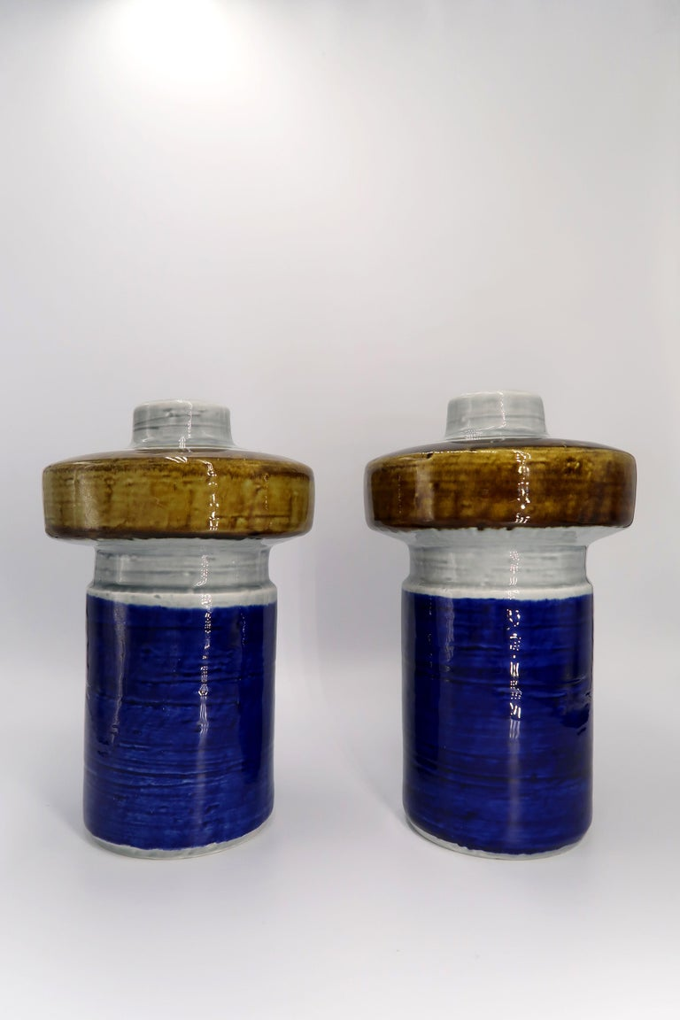 Pair of Scandinavian Mid-Century Modern handmade, hand painted ceramic vases by designer Olle Alberius for Swedish Rörstrand in the 1960s. Cobalt blue base with light grey and hot curry glazed top. Light grey glaze on the inside. From the Titus
