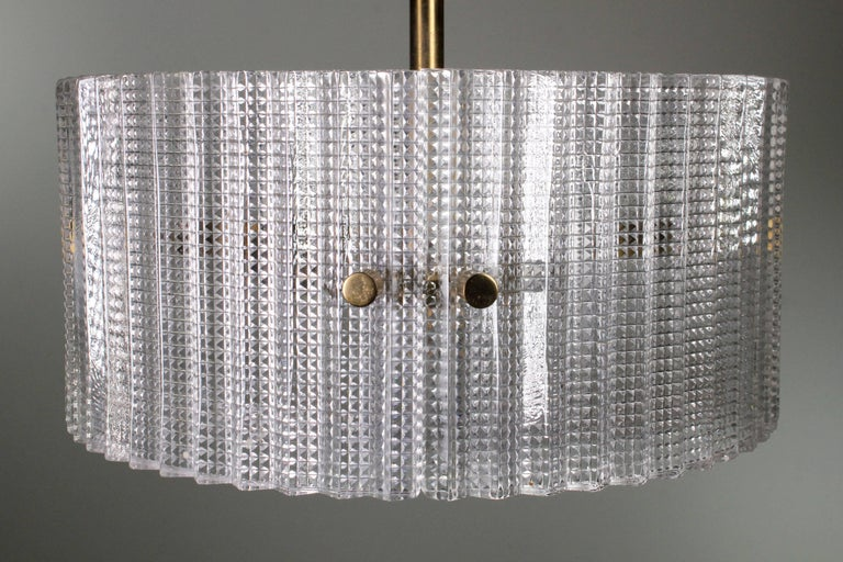 Stunning Swedish Mid-Century Modern textured glass pendant with brass mount and details. Three rounded glass panels held together in a circle with a textured glass base. By acclaimed Swedish designer Carl Fagerlund and manufactured at Orrefors