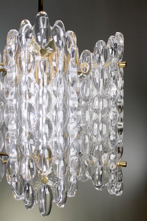 Three large iconic Swedish Mid Century Modern Orrefors chandeliers with six curved plates of bubble textured smooth crystal mounted on brass dividers. Original brass hardware, chain and canopy. By Swedish designer Carl Fagerlund for Orrefors