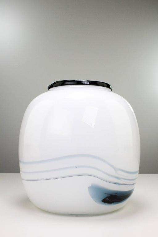 Danish modern smooth round vase with smoky blue and black pattern in milky white glass. From the series Atlantis by Michael Bang for Danish Holmegaard. Manufactured in the town of Næstved on Southern Sealand in Denmark in 1981. In absolutely