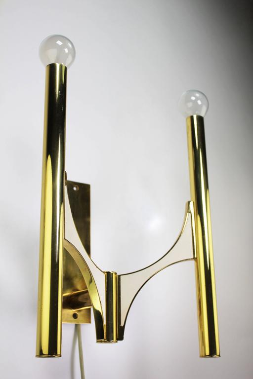 Four elegant, sculptural and minimalist Italian Modern double wall lights with polished brass and white metal sides. Designed by Gaetano Sciolari for Lightolier in the early 1970s. In beautiful condition.  Price is per item.