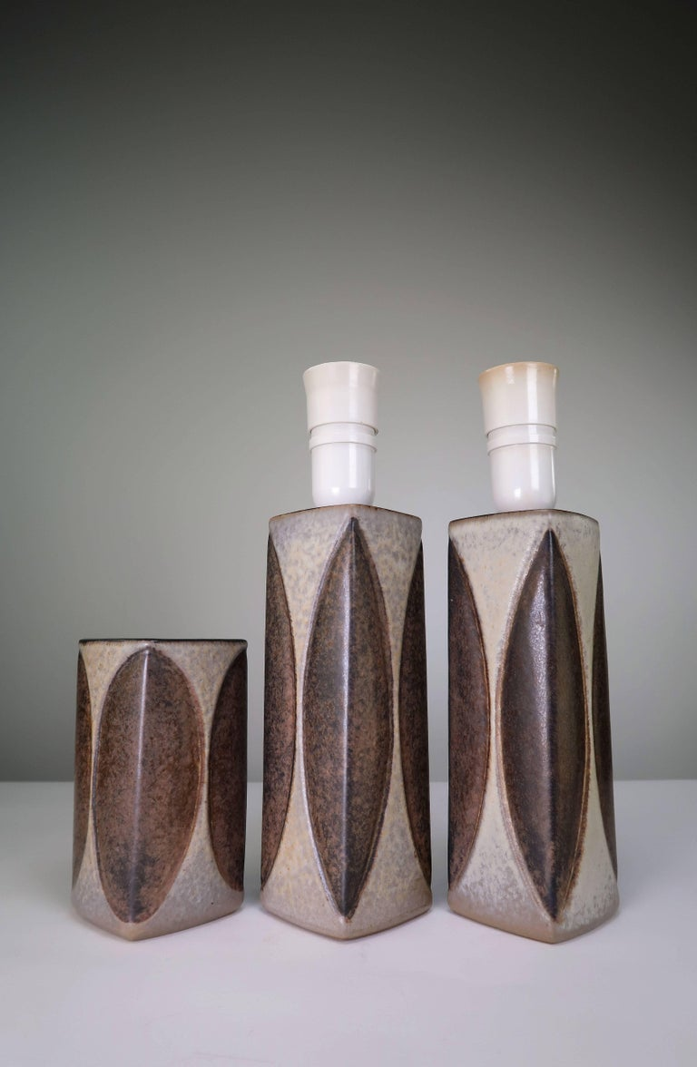 Set of three Danish Mid-Century Modern pieces by manufacturer Michael Andersen & Son. Two table lamps and one vase from the same series. Rectangular and geometric shapes with glaze in grayish cream and chestnut brown. Switch on fittings. Marked and