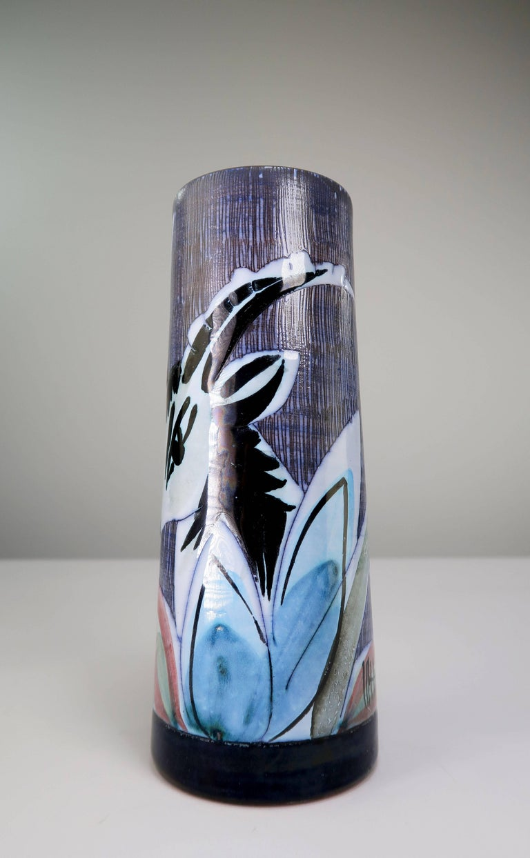 Handmade and hand decorated Swedish Mid-Century Modern tubular ceramics vase depicting the head of a black and white gazelle in wild growing flowers in blue, rose, green and yellow colors. Sgraffito technique on the background of the image. White
