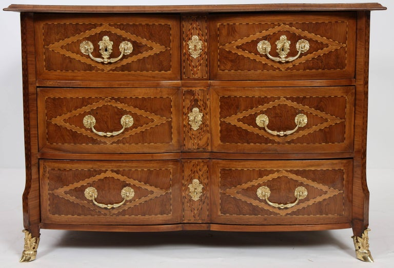 Pretty olive wood marquetry with geometric decoration. It opens with four front drawers of which two in the upper part. Crossbow facade, inlaid wood tops, flat sides. Pull handles, keyholes and crowbars in chiseled and gilded bronze. Restoration