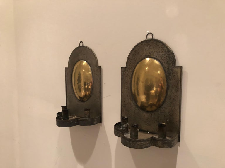 A pair of antique Early American tin sconces with brass reflecting plate. Three candlesticks for taper candles.