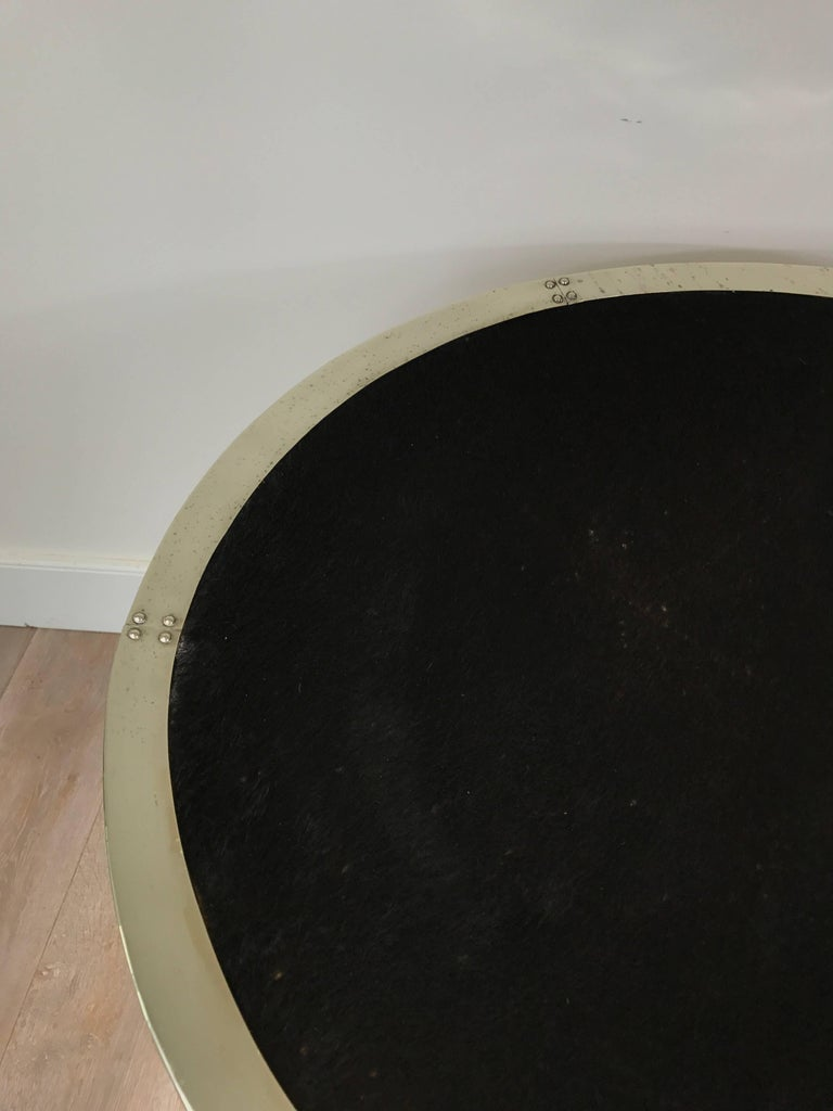 A large black cowhide circular tray with silvered metal surround.
