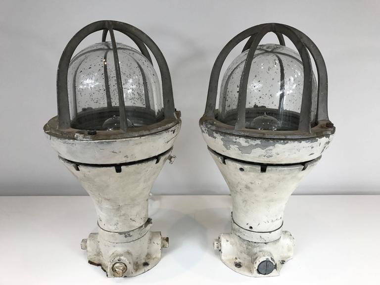 Pair of vintage distressed blast proof lights now wired as table lamps. Heavy steel body with distressed glass globe covers.